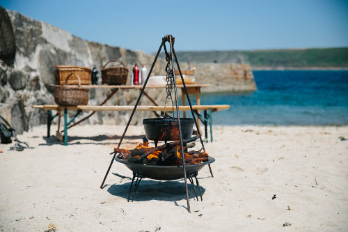 Photograph of a dutch oven hanging on a cast iron tripod over a fire with crab cooking in it
